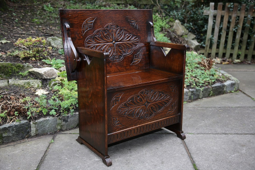 A CARVED OAK MONKS BENCH SETTLE HALL SEAT ARMCHAIR TABLE.