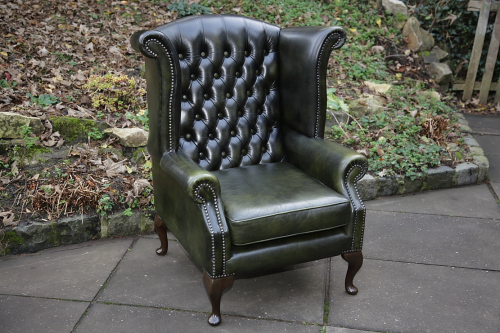 A LEATHER CHESTERFIELD ANTIQUE GREEN WING-BACK ARMCHAIR.