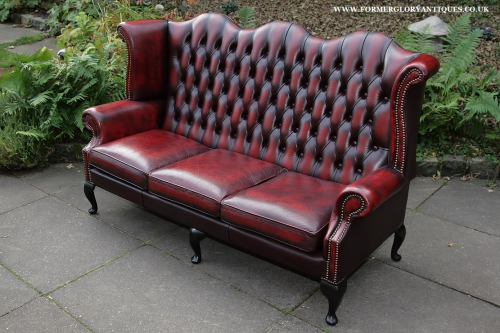 An Oxblood Red Leather Chesterfield Wing Back Armchair Sofa Suite