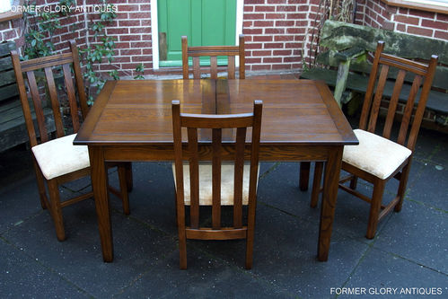 A WOOD BROTHERS OLD CHARM LIGHT OAK EXTENDING DINING TABLE AND FOUR MATCHING UPHOLSTERED CHAIRS