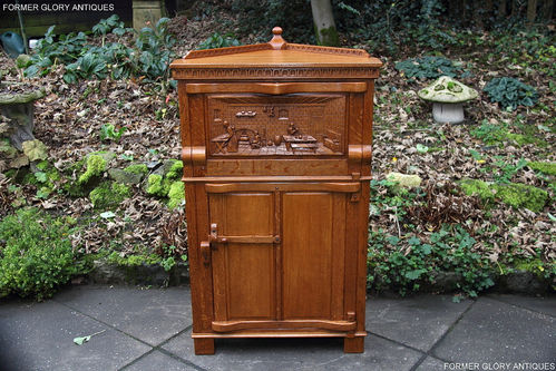 A RUPERT NIGEL GRIFFITHS MONASTIC WOODCRAFT CARVED OAK CORNER DRINKS CABINET