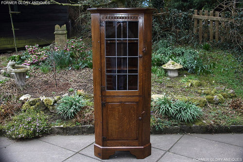 A NIGEL GRIFFITHS CARVED OAK CORNER DISPLAY CABINET