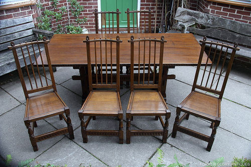 A NIGEL GRIFFITHS SOLID CARVED OAK DINING SET TABLE & SIX STICK BACK CHAIRS
